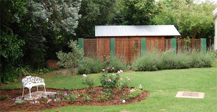 garden shed behind a screen wall