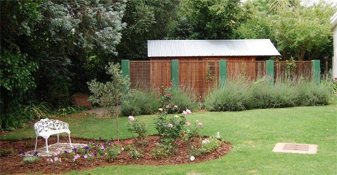 garden shed behind a screen wall
