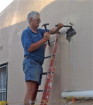 A handyman uses a hammer and chisel to open a hole into the wall so that he can repair a leaking pipe